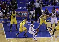 basketball players in maize colored uniforms defend against players in white uniforms