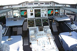 Avionics - The Airbus A380 glass cockpit featuring pull-out keyboards and two wide computer screens on the sides for pilots.