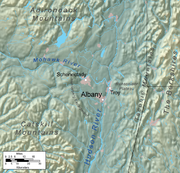 A relief map shows Albany on a flat plain near two rivers, surrounded by mountainous regions.