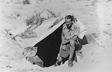 Man in shorts and long socks holding his slouch hat in his hand, in front of a small tent stretched over a hole in the sand.