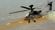 Photograph of an Apache helicopter firing three rockets at a target out of frame.