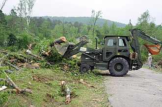 Hot Springs Village, Arkansas - An Arkansas National Guard backhoe clears trees and storm debris from a hard hit area of Garland County, April 26 2011