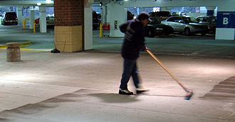 Cleaner - A worker sweeping floor of a parking garage in Atlanta.