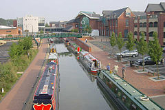 The modern Castle Quay Shopping Centre in Banbury alongside the Oxford Canal, with Banbury Museum in the background.