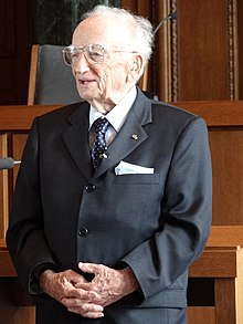 Color photograph taken in 2012 of Ben Ferencz standing in the courtroom where the Nuremberg trials took place. He is dressed smartly in a jacket, shirt, tie, glasses, and his hands are clasped in front.