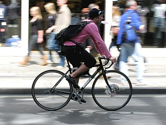 Bicycle messenger - Bicycle courier, London, UK, riding a fixed gear bicycle with spoke cards