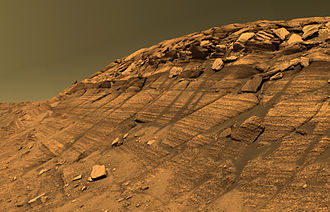 False color - Burns Cliff inside of Endurance crater on Mars. The color is approximate true color because, instead of the red spectral band, infrared was used. The result is a metameric failure in the color of the sky, which is slightly green in the image – had a human observer been present, then that person would have perceived the actual sky color to have a bit more orange in it. The Opportunity rover which captured this image does have a red filter, but it is often not used, due to the higher scientific value of images captured using the infrared band and the constraints of data transmission.
