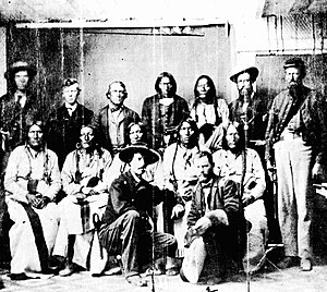 Sand Creek massacre - Some of the identifications of Natives are uncertain. Front row, kneeling, left to right: Major Edward W. Wynkoop, commander at Fort Lyon and later agent for the Cheyennes and Arapahoes; Captain Silas S. Soule, provost marshal, later murdered in Denver. Middle row, seated, left to right: White Antelope (or perhaps White Wolf), Bull Bear, Black Kettle, One Eye, Natame (Arapaho). Back row, standing, left to right: Colorado militiaman, unknown civilian, John H. Smith (interpreter), Heap of Buffalo (Arapaho), Neva (Arapaho), unknown civilian, sentry. Another identification states that Neva is seated on the left and the man next to Smith is White Wolf (Cheyenne).""