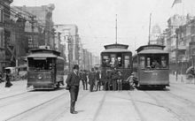"New Orleans, early years of 20th century. Canal Street, about halfway between the intersections of Magazine and Camp, looking lakewards along the neutral ground. Intersection with Camp Street visible at left; Chartres Street at right. Three electric streetcars are on the neutral ground, the route signs of two are visible, showing ""Prytania"" Street line and ""Annunciation"" Street line. A small group of men and boys standing around, including a police officer."