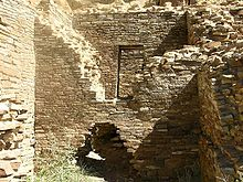Inside daytime view of a ruined and ceiling-less rectangular room. Tawny-beige stacked sandstone bricks compose walls rising from brush-covered ground, the several walls visible in the image are up to perhaps a dozen feet in height. In the wall immediately at center, a triangle-shaped entrance several feet high leads to an adjacent chamber behind, the upper part of the same wall, shaped like an inverted-triangle, has fallen away or otherwise been removed, revealing a rectangular doorway leading to yet another concealed room. At left and right are two similar walls perpendicular to the one at middle.
