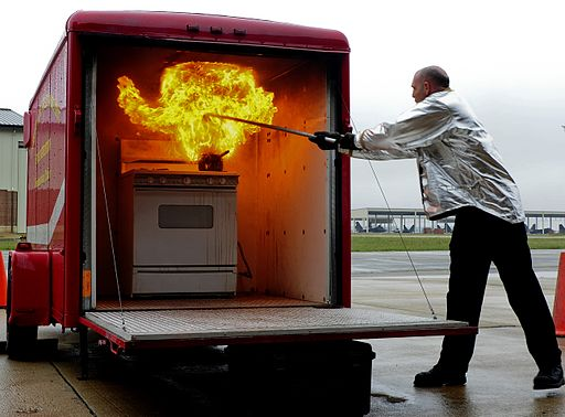 Christian Jacobs, a fire inspector with the 633rd Civil Engineer Squadron, demonstrates techniques for extinguishing a grease fire during Fire Prevention Week at Joint Base Langley-Eustis, Va 131011-F-IT851-014