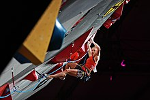 Un mur artificiel d'escalade en surplomb, à l'arrière plan la grimpeuse Petra Klingler en plein effort.