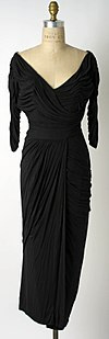 A sleeved black dress held on a mannequin.