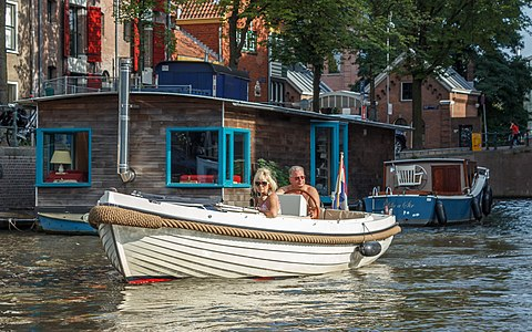 Copule in boat passes houseboat in canals of Amsterdam