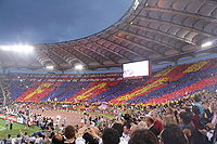 A full stadium, with fans holding up yellow, blue and red cards to make a giant mosaic.