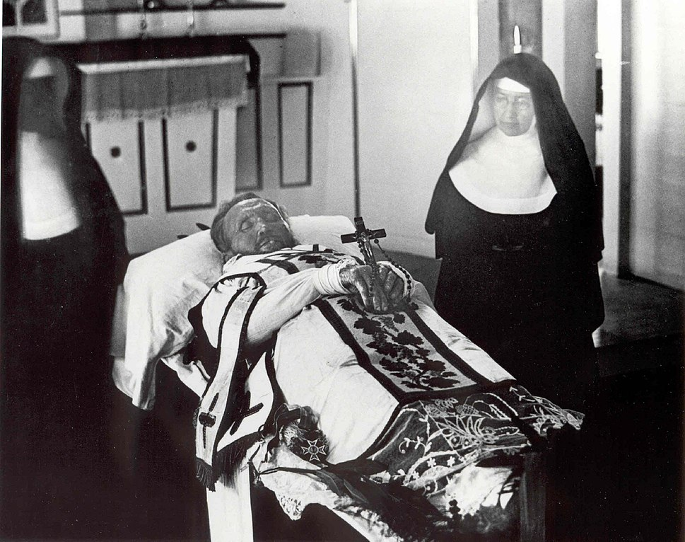 Father Damien on his funeral bier with Mother Marianne Cope by his side
