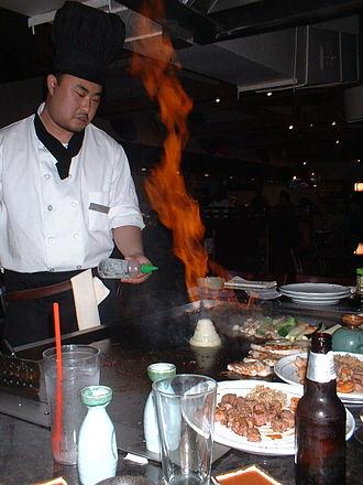 Teppanyaki - Chef preparing a flaming onion volcano