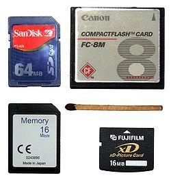 Modelos diversos de cartões de memória ao lado de um fósforo; em sentido horário a partir do topo, CompactFlash, xD-Picture Card, MultiMediaCard e Secure Digital Card.