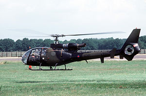 A small camouflaged helicopter hovers, just off the ground, over a field.