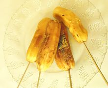 Four grilled bananas on wooden sticks