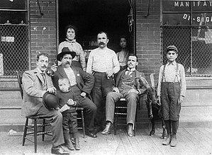 Giosue Gallucci - Giosuè Gallucci and wife Assunta (centre), John Russomano (right) and Luca Gallucci (small boy to the left), outside Gallucci's East 109th Street cigar business, c. 1900