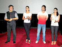 Govinda and three other people, standing on a red carpet
