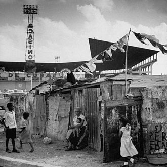 Cuba - Slum (bohio) dwellings in Havana, Cuba in 1954, just outside Havana baseball stadium. In the background is advertising for a nearby casino.