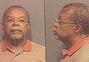A pair of mugshots giving front and profile views of a middle-aged African American man with very short-trimmed dark hair very short-trimmed grey goatee and mustache, a neutrally nondescript or matter-of-fact expression on his face, wearing very lightweight wire-rimmed eyeglasses and an orange-and-white variegated-pinstripe polo shirt.