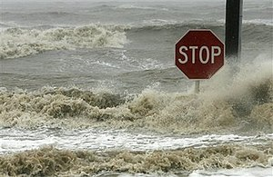 Waves crash against a stop sign on Beach Boule...
