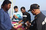 Indian Navy officers serve meals on deck to evacuees (01).JPG