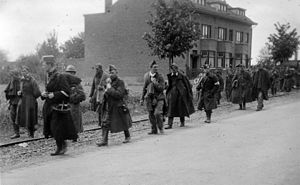 Belgian soldiers taken prisoner by the Germans marching down a road