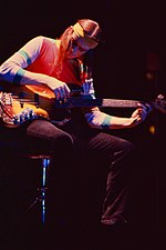 Una fotografía en color de Jaco Pastorius sentado en un taburete y tocando un bajo