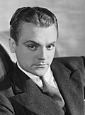 Black-and-white photo of James Cagney in 1930--a white man with serious features and an arched eyebrow, dark eyes and hair combed back, wearing a suit and around 30 years of age.