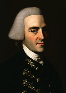 Half-length portrait of a man with a hint of a smile. His features suggests that he is in his 30s, although he wears an off-white wig in the style of an English gentleman that makes him appear older. His dark suit has fancy embroidery.