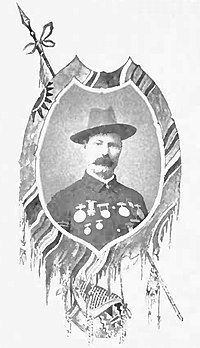 Framed portrait of a white man with a mustache, cavalry hat, and an array of medals across his chest