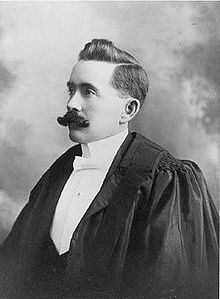 A formal portrait of a left-facing man with a moustache, wearing barrister's robes