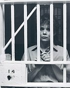 A woman with short hair, wearing shirt, while holding the bars of a fictional prison.