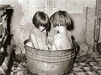 Two children bathing in a small metal bath tub