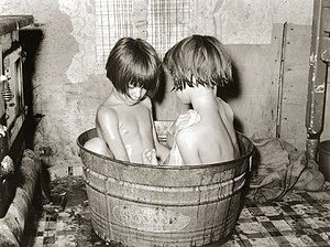 Two children bathing in a small metal bath tub