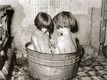 English: Kids bathing in a small metal tub. Th...