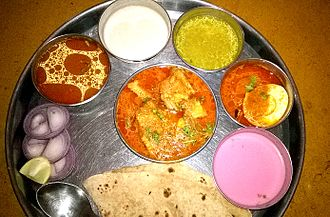 Maharashtrian cuisine - This meal has meat in red and white gravies, solkadhi (pink), chapatis, lemon and onion