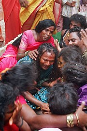 A group of seated transvestite men and/or eunuchs dressed in saris mourn.