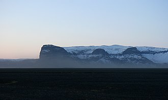 Outwash plain - Unimpeded by topographic obstructions, sand-bearing katabatic winds can be fierce enough on Skeiðarársandur to strip paint from cars. Here, sand is blown in the air in front of the peak Lómagnúpur.