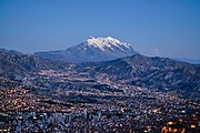 A large, snow-capped mountain behind an evening cityscape.