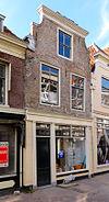 foto van Pand met gewijzigde en geverfde trapgevel met boven de vensters van de verdieping ontlastingsbogen