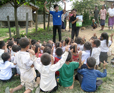 Young students learn some words of Lao sign language from Suliphone, a deaf artist. This was one of several activities at a school book party sponsored by Big Brother Mouse, a literacy project in Laos where Suliphone works.