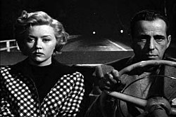 Black-and-white image of a man and woman, both with downcast expressions, sitting side by side in the front seat of a convertible. The man, on the right, grips the steering wheel, he wears a jacket and a pullover shirt. The woman wears a checkered outfit. Behind them, in the night, the road is empty, with a two widely separated lights way off in the distance.