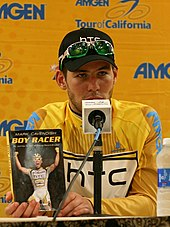 Cavendish sitting in front of a microphone holding a copy of his book Boy Racer