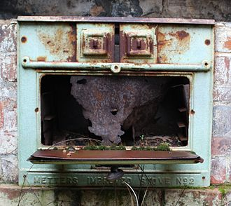 Metters Limited - An abandoned Metters Improved Stove No 2. A small fire was built behind the sliding doors at top centre.