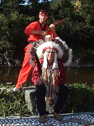 Okichitaw - George Lépine (standing) with gunstock war club and Vern Harper (seated) with Eagle feather